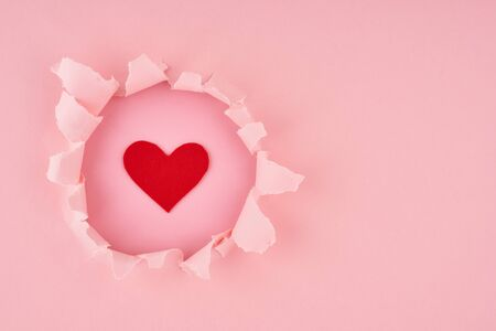 Valentine's Day. A ripped hole and red heart in a bright pink textured background, concept of rupted paper with copy space. Long width side banner Stockfoto - 134111486