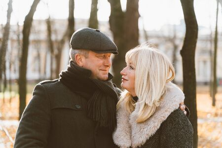 Closeup portrait of a happy blonde mature woman and a beautiful brunette middle-aged man looking at each other's eyes.