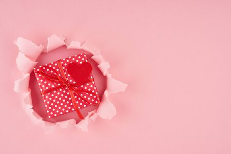 Valentines Day. A ripped hole and red heart with gift box in a bright pink textured background, concept of rupted paper with copy space. Long width side banner Stockfoto