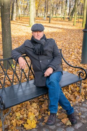 Closeup portrait of a handsome middle-aged full-length brunette man. A mature handsome man of 45-50 years walks in an autumn park in warm clothes, in a coat and cap 版權商用圖片