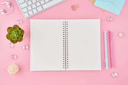 Blank notepad page in bullet journal on bright pink office desktop. Top view of modern bright table with notebook, stationery. Mock up, copy space, concept for diary, top view