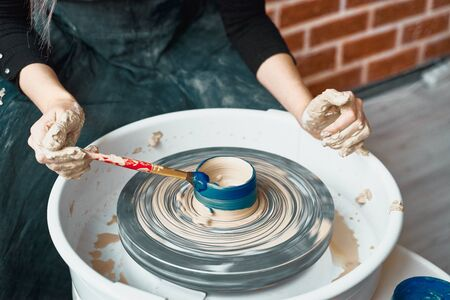 Unrecognisable woman making ceramic pottery on wheel, paints blue. Concept for woman in freelance, business. Handcraft product. Earn extra money, side hustle, turning hobbies into cash, close up Stock fotó