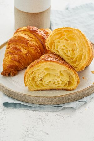 Two delicious croissants on plate and hot drink in a mug.