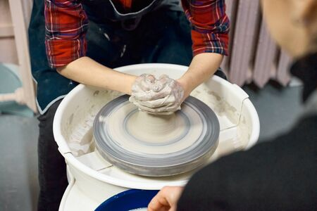 Woman making ceramic pottery on wheel, hands closeup. Concept for woman in freelance, business, creative hobby. Earn extra money, side hustle