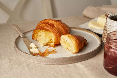 One delicious croissants on plate and hot drink in mug. Morning French breakfast with fresh pastries and jam. Light gray background, top view