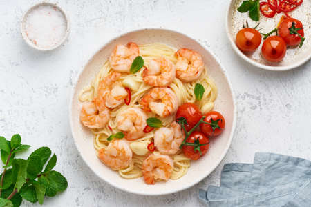 Pasta bavette with fried shrimps, bechamel sauce, mint leaf, garlic, tomatoes, chili on white plate, top view, italian cuisine.