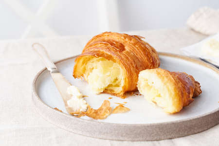 Coffee with croissant. Bright sunny morning, leisurely breakfast with fresh pastries, slice of croissant, butter and jam. Traditional french breakfast. White wall, white chair. Side view Stock fotó