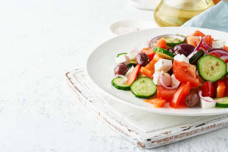 Greek village salad horiatiki with feta cheese, olives, cherry tomato, cucumber and red onion, vegeterian mediterranean food, low calories dieting meal, copy space