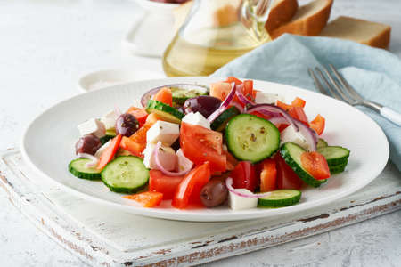 Greek village salad horiatiki with feta cheese, olives, cherry tomato, cucumber and red onion, vegeterian mediterranean food, low calories dieting meal, side view