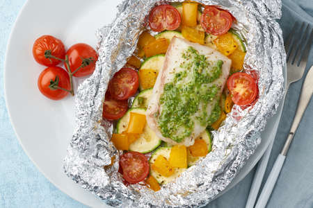 Foil pack dinner with white fish. Oven baked fillet of cod, pike perch with vegetables
