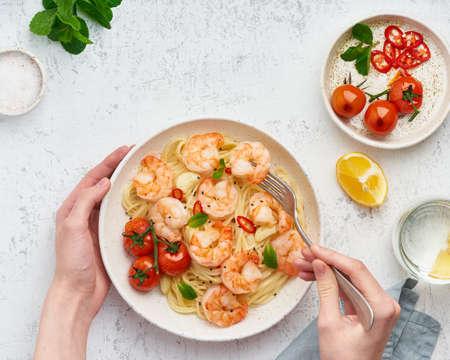 Pasta bavette with fried shrimps, bechamel sauce. Woman hands in frame, girl eats pasta, top view Banque d'images