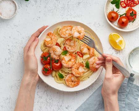 Pasta bavette with fried shrimps, bechamel sauce. Woman hands in frame, girl eats pasta, top view
