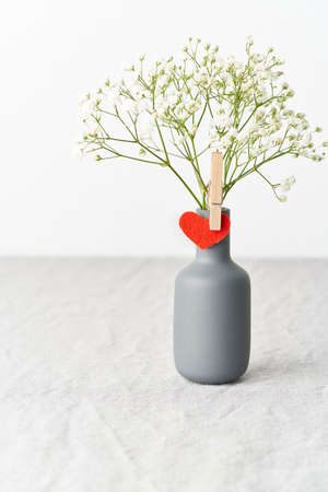 Valentines Day. Delicate white flowers in a vase. Red felt heart - symbol of lovers.