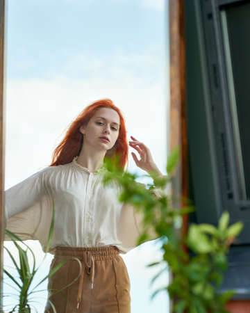 Beautiful red-haired woman looks at reflection in mirror on street