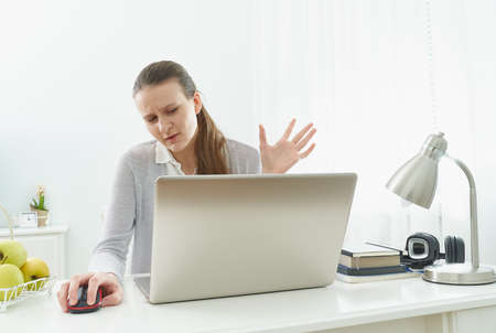 Girl listens or looks at information on computer with disbelief. Skeptical expression. Fake news.