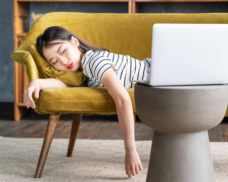 Young Asian girl fell asleep oncouch in front oflaptop. Cute bored woman watching boring movie