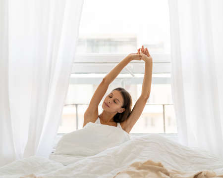 Young woman stretching in bed after wake up, entering new day happy and relaxing after good night sleep. Sweet dreams, good morning, weekend, holidays concept