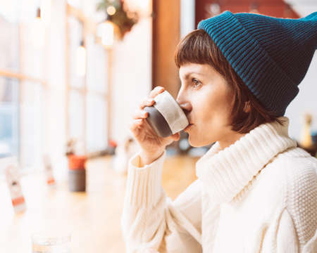 Beautiful female in cafe in Christmas winter holidays in lights of garland. Mature woman drinking coffee and looking out window, cold weather, dark backdrop