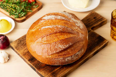Whole loaf of freshly baked white wheat bread on wooden board on home kitchen table