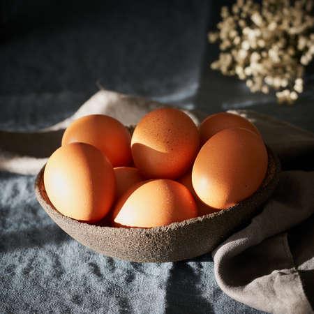 Bowl of brown eggs on dark blue table