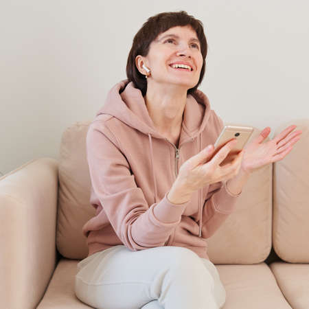 Portrait of mature woman recording audio message, speaking to microphone of mobile phone. Middle-aged female in pastel home clothes speaking by audio-chat. Remote education, training and mentoring