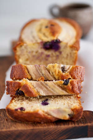 Banana bread, slice of cake with banana and blueberries. Morning breakfast with coffee on light gray linen textile tablecloth on table, Lifestyle still life food. Side view. Close up, macro, vertical