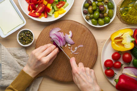 Vegetarian food. Chopping onion, cutting vegetables for greek salad horiatiki. Woman hands with knife on wooden cutting board slicing chop of vegetables. Homemade vegan food, top view