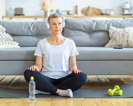 Senior woman sit cross-legged in headphones listen music in living room. Relax after exercising fitness. Emotional and spiritual health. Well-being, wellness with meditation. Enjoying good moments