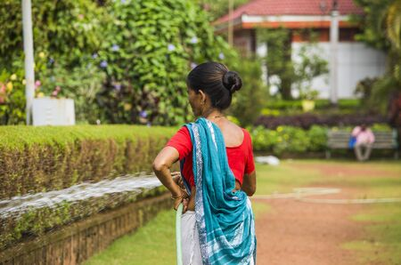 look after: woman the gardener waters the gardens
