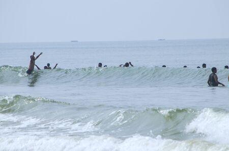 hindues: la gente nadar en las olas en el mar