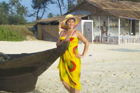 pareo: girl on a beach smiles in a hat