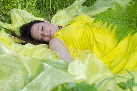 sleeps: The young girl sleeps on yellow matter in nature