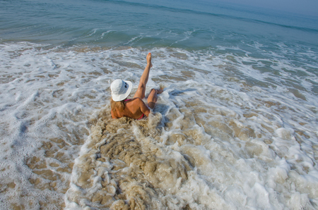 the girl in the hat swims in the sea in the waves 版權商用圖片
