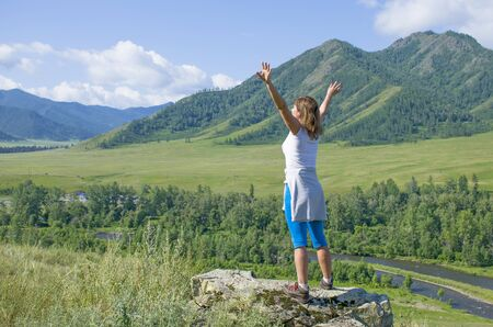 girl with the raised hands in the mountains