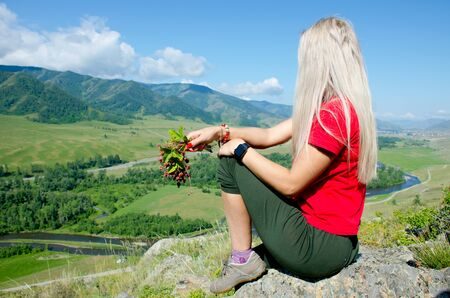 The girl sits on mountain top with berry in a hand