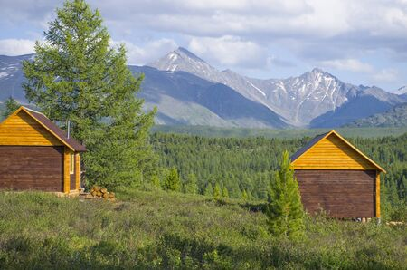 House for rest in taiga against the background of the high mountains of Altai in Russia