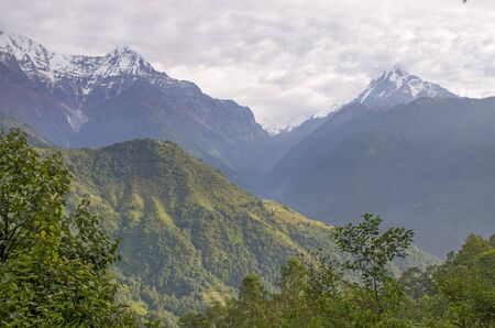 The peaks of the mountains of Nepal among the trees are the landscape of the Himalayas Archivio Fotografico