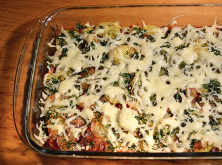 casserole in a glass form grated cheese on top and herbs
