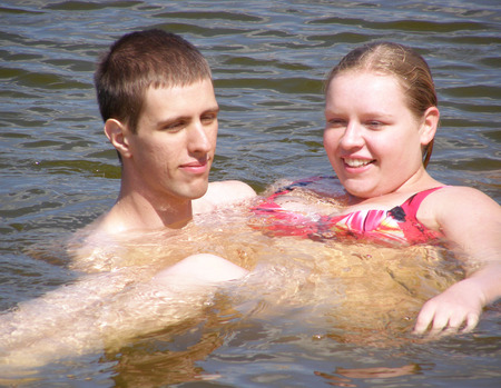 plump: Happy couple. A young man standing in the water, holds on hands chubby young woman