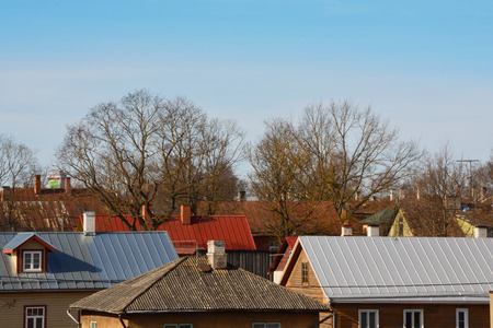 Roofs of old houses with chimneys. Early spring Stock Photo