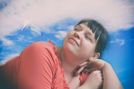 Chubby girl on a background of blue sky and seagulls dreaming about something pleasant. Photo toned in retro style Stock Photo