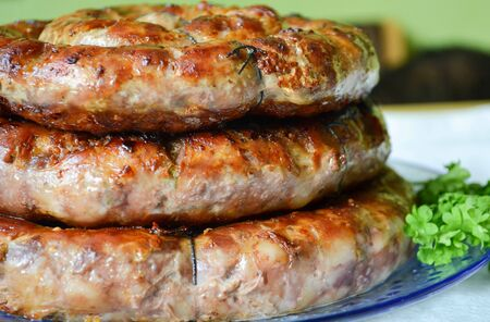 Homemade sausage rings on a plate, side view