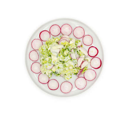 Vegetable salad with mayonnaise on a white plate