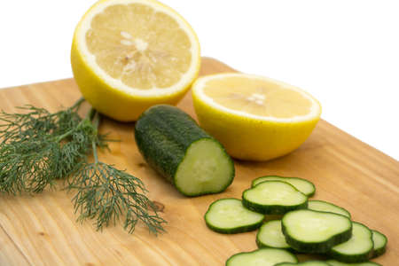 Cucumber, two halves of lemon and dill sprigs on a wooden board