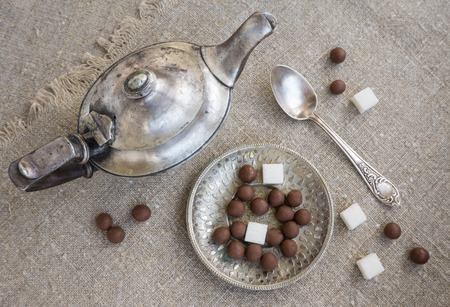 dragees: Ancient silver teapot, sugar cubes and chocolate dragees on canvas