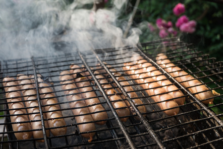 grate: Some fried sausages on the grill grate