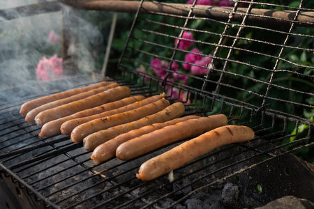 to grate: Some fried sausages on the grill grate