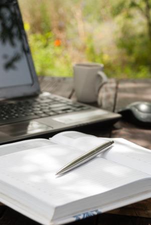 ball pens stationery: Pluma, cuaderno y computadora portátil en el fondo del jardín. Foto de archivo