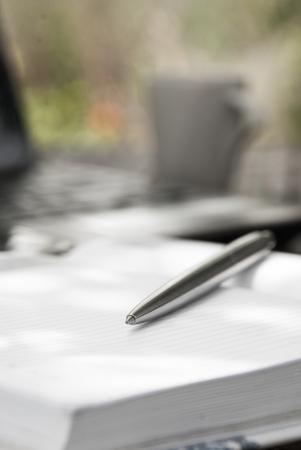 ball pens stationery: Pluma, cuaderno y computadora port�til en el fondo del jard�n. Foto de archivo