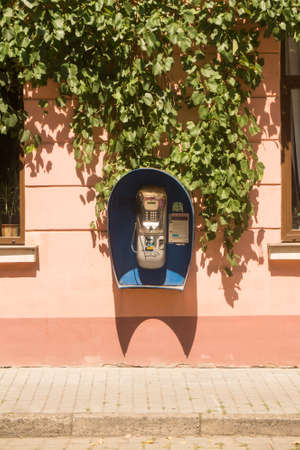 payphone: Payphone on the wall of an old house in Chernivtsi, Ukraine. In the upper part of the wall - vine branches